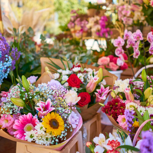 A closeup of colorful flower bouquets in containers at an outdoor shop